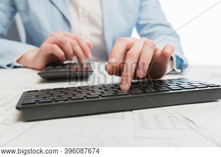 Business woman using calculator and computer keyboard at office