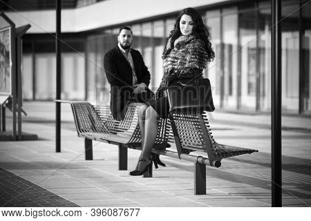 Happy young fashion couple sitting on bench  Stylish trendy man in classic black coat and woman in fox fur jacket