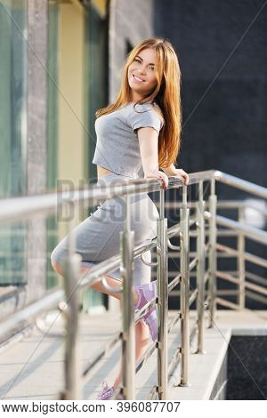Young woman leaning on railing Stylish fashion model with long straight hairs in gray crop top and skirt suit