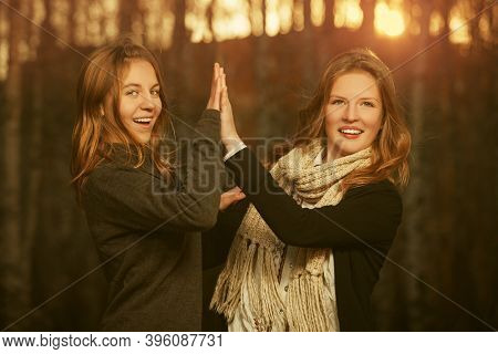 Two happy young fashion girls in black pullover and scarf walking outdoor