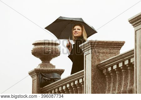 Happy young fashion woman with umbrella walking on city street Stylish female model in classic black coat