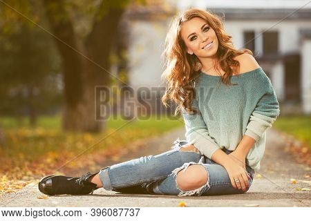 Happy young woman with long curly hairs sitting on sidewalk  Stylish fashion model in blue pullover and ripped jeans