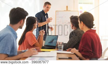 Young male colleague briefing to his other friends using graph on whiteboard