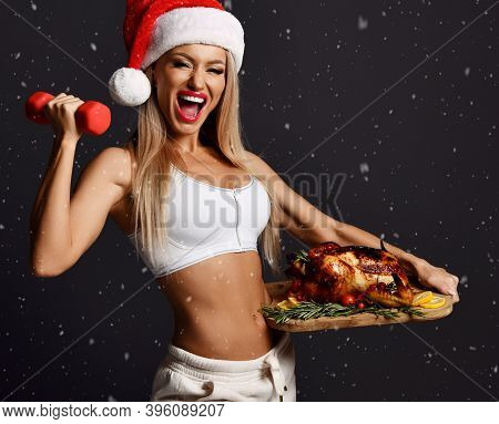 Young Happy Beautiful Sexy Blonde Fitness Woman In White Clothes And Santa Hat Standing With Roasted