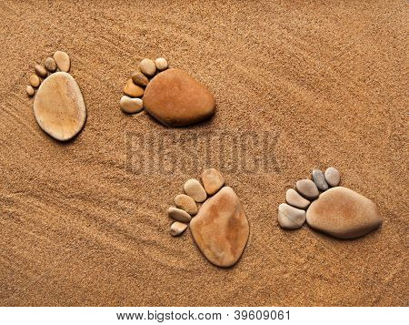 trace feet steps made of a pebble stone on the sea sand backdrop