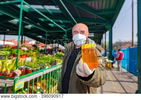 Seller Is Offering, Selling Fresh Honey At Outdoor Flea Market Protected Against Virus Covid-19, Cor