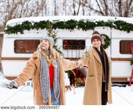 Romantic Couple Camping At Winter With Modern Campervan, Enjoying Snow And Cold Weather, Holding Han