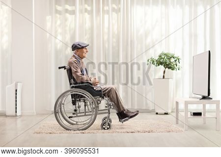 Full length profile shot of an elderly man in a wheelchair watvhing tv in a living room at home