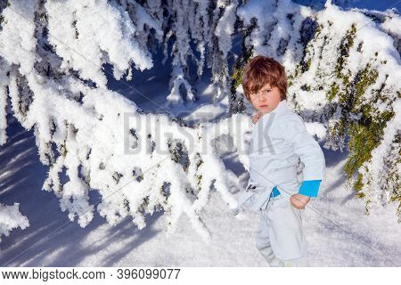 Handsome boy in white judo uniform training for judo. Winter coniferous forest. Huge spruce covered with snow. New Years is soon