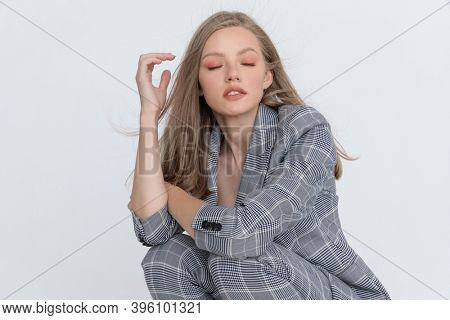 crouched young lady with closed eyes in gray checkered suit holding arms in a fashion pose on light gray background in studio