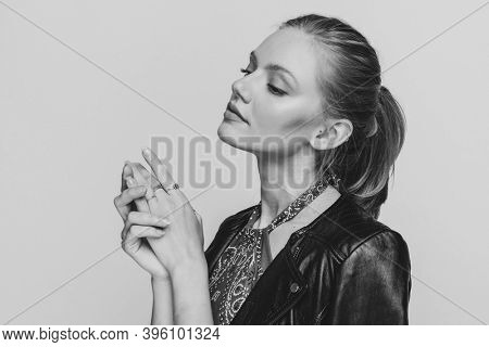 side view of young woman in leather jacket looking to side, touching hands and posing on black and white background in studio