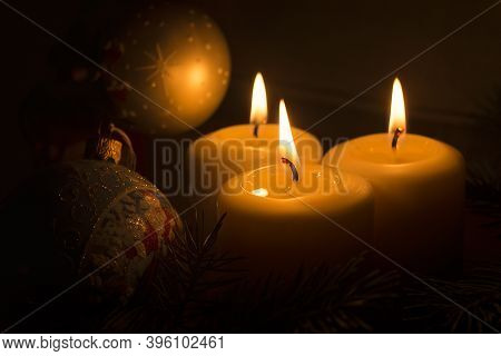 White Candles With Christmas Tree Branches And Christmas Tree Toys On A Dark Background. The Candle