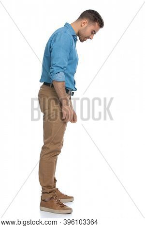 sie view of a sexy casual man looking down at something against white background
