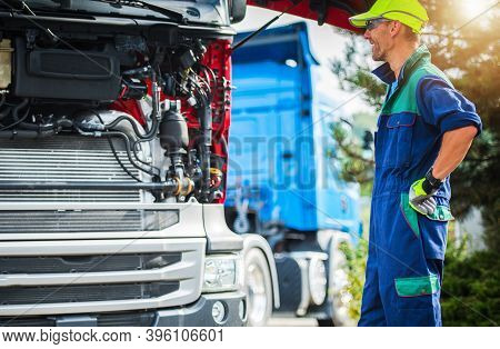 Happy Smiling Caucasian Professional Truck Mechanic In His 30s Staying Next To Semi Truck Tractor Wi