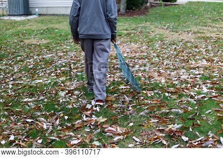 An African-american Man Raking Leaves In A Front Lawn In Autumn