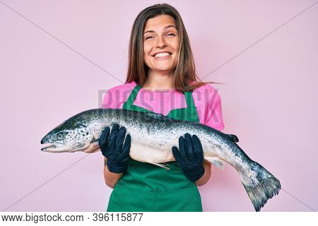 Beautiful caucasian woman fishmonger selling fresh raw salmon smiling and laughing hard out loud because funny crazy joke.