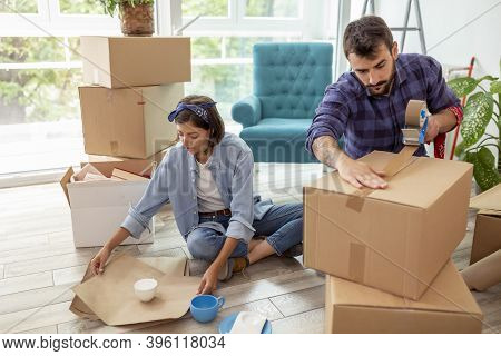 Couple In Love Packing Things Into Cardboard Boxes, Getting Ready For Relocation - Man Taping Boxes