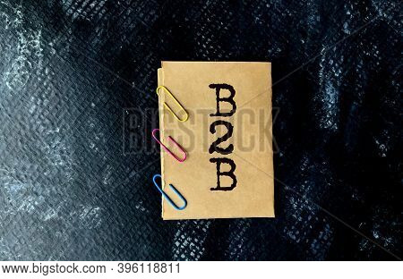B2b On A Craft Piece Of Paper With Paper Clips On A Black Background. Abbreviation B2b, Business And