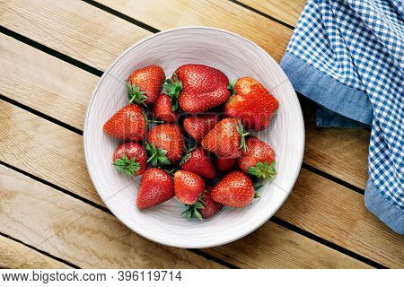 Delicious juicy strawberries on the plate with wooden background.