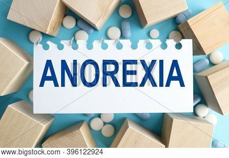 Anorexia. On A Blue Background, On White Paper Near Wooden Cubes. Medicine Concept