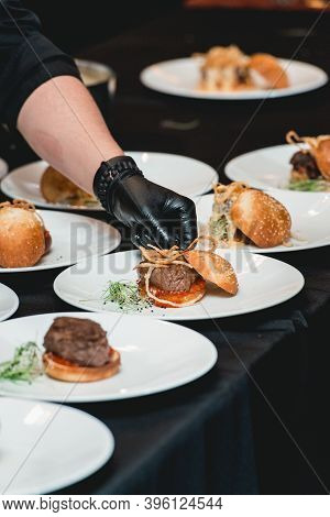 Chef In A Black Gloves Serving A Burgers On The Table In A Restaurant