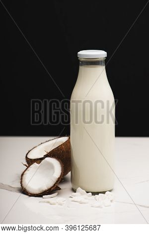Coconut Halves, Flakes, And Bottle Of Milk On White Surface Isolated On Black