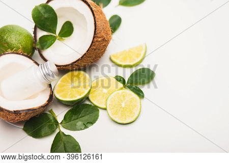 Sliced Lime, Rose Leaves, Coconut Halves And Milk On White Background