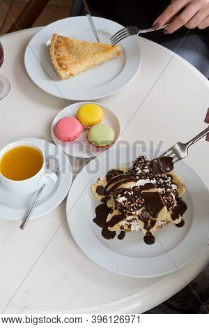 Tea Served With Macarons, Pie And Oancakes In A Cafe