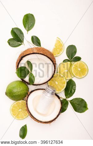 Top View Of Lime, Coconut Halves, Bottle Of Lotion And Rose Leaves On White