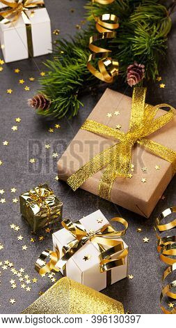 Christmas Concept. Bright Gift Wrap With Gold Ribbon, Christmas Branches And Confetti Stars On A Dar
