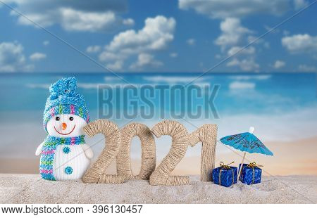 Merry Christmas And Happy New Year. Snowman And The Inscription 2021 In The Sand On The Beach