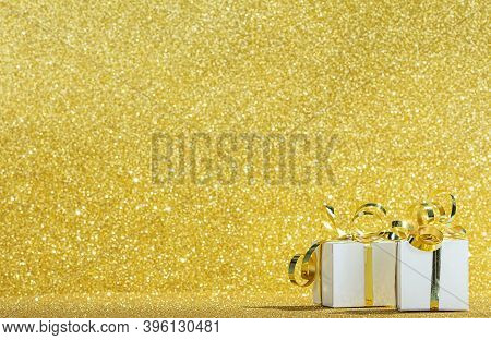 White Gift Boxes With Ribbon On Sparkling Gold Background With Glitter