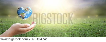 Hand Holding Heart Shaped Earth Globe And  Over Blurred Nature Background. Elements Of This Image Fu