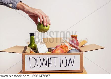 Man Putting An Aple Into A Box Full On Canned And Packed Food