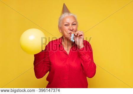 Senior Hispanic Woman Celebrating Her Birthday With Balloon.