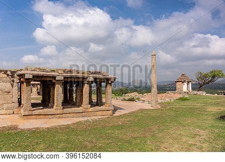 Hampi, Karnataka, India - November 4, 2013: Ruins At Moola Virupaksha Temple Behind Green Lawn And U
