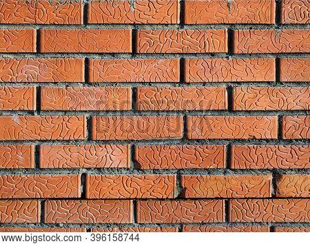 The Wall Is Made Of Decorative Red Bricks. On The Brick, Neat Grooves Are Visible, Which Fold Into A