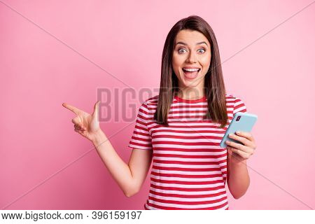 Photo Portrait Of Amazed Woman Keeping Cellphone Pointing With Finger At Copyspace Isolated On Paste