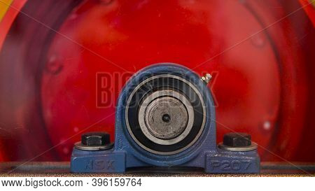 Close-up Of Rotating Red Cylinder. Media. Rotating Industrial Drum Is Red In Color. Large Screws Wit