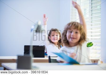 Cute Little Pupils Raising Hands During Lesson. Children In Classroom At School