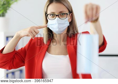 Businesswoman In Red Suit Holding Medical Protective Mask In Office. Mask Compliance During Covid-19
