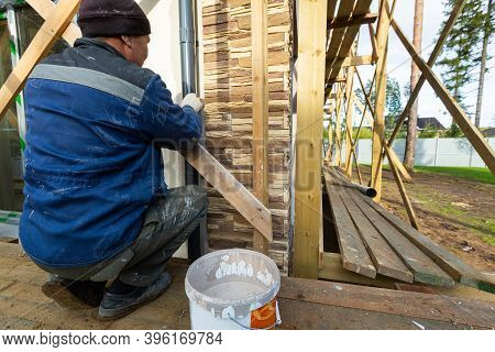 Worker In Protective Gloves Is Painting By The Brush The Facade House That Is Under Construction, Re