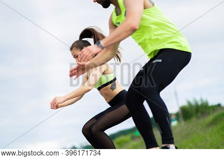 Sportive Young Couple Exercizing Jumping Or Doing Squats Outdoor, Couple Workout