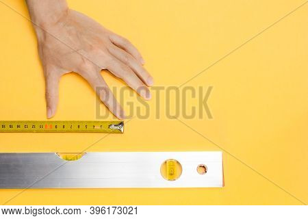 Hand, Measure Tape And Aluminium Spirit Level Tool On Yellow Background. Construction Fluid Level Wi