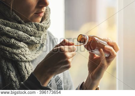 Sick Woman With Scarf Around The Neck Taking Cough Syrup At Home