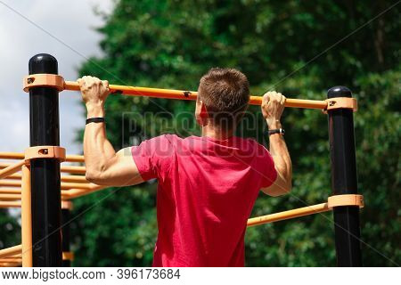 Portrait Of Strong Sportsman Doing Strength Exercises. Athlete Pulling Up On Horizontal Bar On Athle