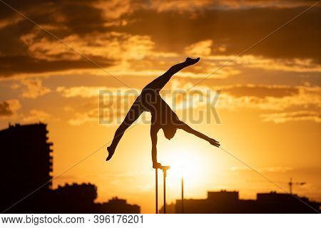 Flexible Female Circus Artis Keep Balance On One Hand On The Rooftop Against Dramatic Sunset And Cit