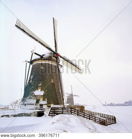 The Netherlands, Kinderdijk, Windmills In Snow At Sunrise. This Is An Unesco World Heritage Site