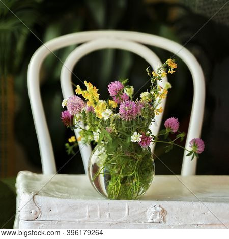 Vintage White Vienna Chair, Bright Wildflowers Bouquet With Clover In Glass Vase