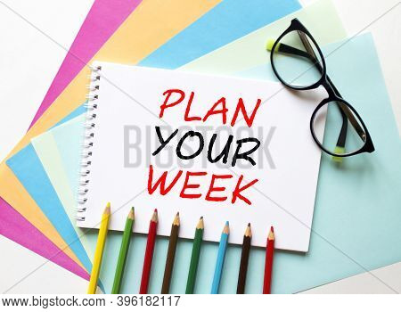 The Notebook Is On Colored Paper With Text Plan Your Week. Colored Pencils And Eyeglasses